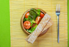 Fresh vegetable salad in wooden bowl on bamboo napkin with crisp. Fresh vegetable salad of salad leaves and tomatoes Stock Photography
