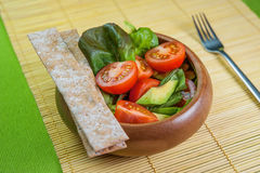 Fresh vegetable salad in wooden bowl on bamboo napkin with crisp. Fresh vegetable salad of salad leaves and tomatoes Royalty Free Stock Images