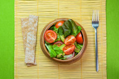 Fresh vegetable salad in wooden bowl on bamboo napkin with crisp. Fresh vegetable salad of salad leaves and tomatoes Stock Images