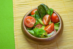 Fresh vegetable salad in wooden bowl on bamboo napkin with crisp. Fresh vegetable salad of salad leaves and tomatoes Royalty Free Stock Image