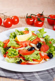 Fresh vegetable salad on the wooden table. Fresh vegetable salad with mushrooms, apples, tomatoes, lettuce, celery and olives on the wooden table Stock Photo
