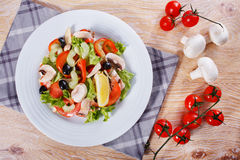 Fresh vegetable salad on the wooden table. Fresh vegetable salad with mushrooms, apples, tomatoes, lettuce, celery and olives on the wooden table Royalty Free Stock Photo