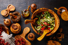 Fresh vegetable salad and wooden tableware. Fresh vegetable salad in olive wood bowl and wooden tableware on black burned wooden background Royalty Free Stock Images