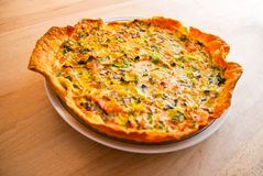 Fresh vegetable and salmon quiche tart. Freshly baked vegetable and salmon quiche tart on a white plate and wood countertop Stock Photo