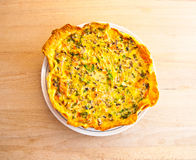 Fresh vegetable and salmon quiche tart from top. Freshly baked vegetable and salmon quiche tart on a white plate and wood counter-top shot from above Stock Photo