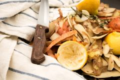 Fresh vegetable scraps with knife and towel. Fresh vegetable scraps with peeler, knife and towel, house waste/compost management concept Royalty Free Stock Images