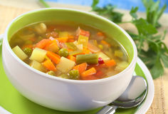 Fresh Vegetable Soup. Made of green bean, pea, carrot, potato, red bell pepper, tomato and leek in bowl with parsley in the back (Selective Focus, Focus on the Royalty Free Stock Image