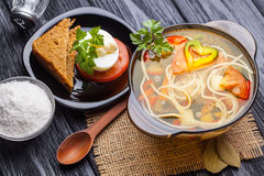 Fresh vegetable soup with noodles in a pot on black Royalty Free Stock Photos