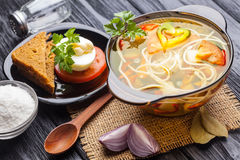 Fresh vegetable soup with noodles in a pot on black Stock Photos