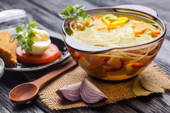 Fresh vegetable soup with noodles in a pot on black Royalty Free Stock Image