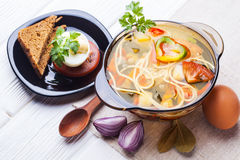 Fresh vegetable soup with noodles in a pot on white Stock Images