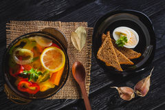 Fresh vegetable soup in a pot on black background Stock Photos