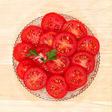Fresh vegetable tomato slices in a glass dish. Fresh vegetable tomato slices in a glass dish isolated on a white background Stock Photo