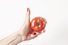 Fresh vegetable tomato in woman hand, fingers with red nails manicure, isolated on white background, healthy lifestyle concept. Royalty Free Stock Photos