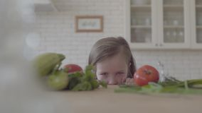 Fresh vegetable zucchini, tomatoes and greens laying on the table. The cute little girl looks from the table, hiding stock video footage
