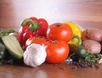 Fresh vegetables. Tomatoes, cucumbers, garlic and others on a wooden table Royalty Free Stock Images