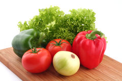 Fresh vegetables. Salad, red paprika, green paprika, tomatoes and onion on kitchen desk Royalty Free Stock Images