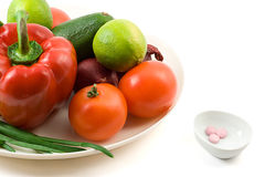 Fresh vegetables against vitimin pill Stock Images