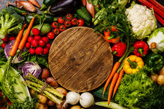 Fresh vegetables around wooden cutting board. Fresh vegetables around round wooden cutting board copy space Royalty Free Stock Photo