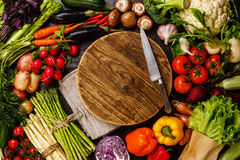 Fresh vegetables around wooden cutting board Stock Photos
