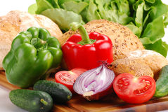 Fresh vegetables and bakery products on breadboard. Composition with vegetables and bakery products on breadboard on white background Stock Photos