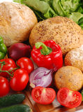 Fresh vegetables and bakery products on breadboard. Composition with vegetables and bakery products on breadboard Stock Photos