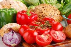 Fresh vegetables and bakery products on breadboard Royalty Free Stock Photography
