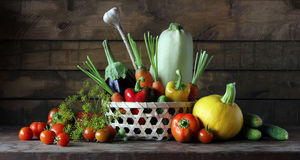 Fresh vegetables in basket, still life in rustic style. Fresh vegetables in basket on the table: tomato, pepper, cucumber, zucchini, eggplant and others. Still Royalty Free Stock Photography
