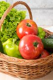 Fresh vegetables in basket. Tomato, cucumber, pepper and lettuce. Fresh vegetables covered with water drops in brown basket. Organic large tomatoes, cucumber Royalty Free Stock Image