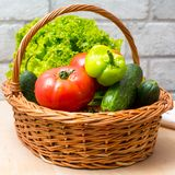 Fresh vegetables in basket. Tomato, cucumber, pepper and lettuce. Fresh vegetables covred with water drops in basket. Organic Tomatoes, cucumber, pepper and Royalty Free Stock Images