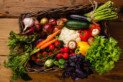 Fresh vegetables in basket. On wooden background royalty free stock images