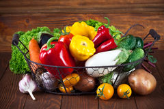 Fresh vegetables in basket on wooden board Stock Images