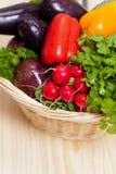 Vegetables. Fresh vegetables in basket on wooden table Stock Images