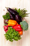 Vegetables. Fresh vegetables in basket on wooden table Royalty Free Stock Photography