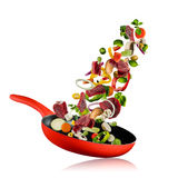 Fresh vegetables and beef meat flying into a pan on white background Stock Images