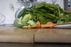 Fresh vegetables being chopped on a cutting board. Spinach, broccoli and sweet potatoes being prepared for freshly made soup royalty free stock images