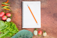 Fresh vegetables with blank notebook on wooden background. Stock Photos