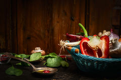 Fresh vegetables in blue basket , cooking spoon and ingredients on rustic kitchen table over wooden background. Stock Photography