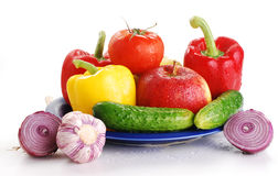 Fresh vegetables on blue plate. Freshly washed vegetables with visible drops of water isolated on white Royalty Free Stock Image