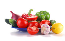 Fresh vegetables on blue plate. Vegetables with visible drops of water isolated on white Stock Photography