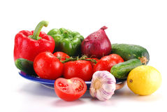 Fresh vegetables on blue plate. Freshly washed vegetables with visible drops of water isolated on white Stock Photography