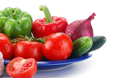Fresh vegetables on blue plate. Freshly washed vegetables with visible drops of water isolated on white Stock Photo