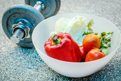 Fresh Vegetables in a bowl and dumbbells Stock Image