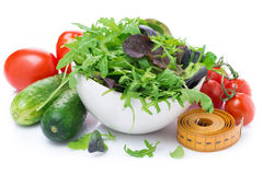 Fresh vegetables, a bowl of green lettuce and measuring tape Royalty Free Stock Photography