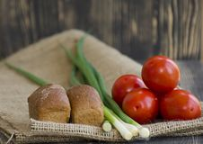 Fresh vegetables and bread on burlap background stock images