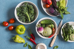 Fresh vegetables - broccoli, peppers, tomatoes, eggplant, squash, turnips on a blue background, top view. Stock Image