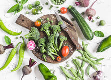 Fresh vegetables - broccoli, zucchini, peppers, beets, green beans and peas, tomatoes on a light background. Raw ingredients for c Stock Photo
