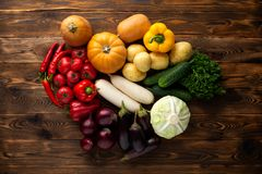 Fresh vegetables on a brown wooden background stock photos