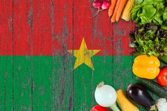 Fresh vegetables from Burkina Faso on table. Cooking concept on wooden flag background.  stock images