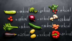Fresh vegetables and calories table isolated on black. Healthy lifestyle concept royalty free stock photo